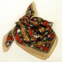 Wielokolorowa apaszka gawroszka z jedwabiu z wyrazistym, roślinnym wzorem.