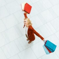 overhead view of attractive happy girl with colorful shopping bags