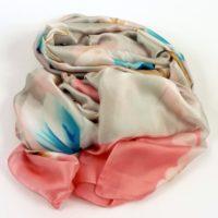 Cienki, jedwabny szal damski w pastelowych odcieniach z kwiatowym wzorem.
